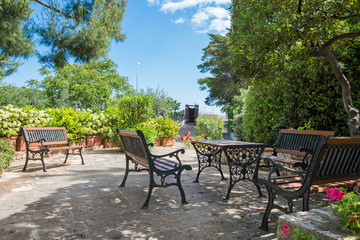 Vintage Italian style garden furniture set up on a terrace next to a villa. Bright red flowers in the front.