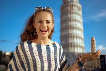 smiling elegant woman showing leaning tower of Pisa souvenir