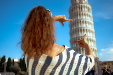 woman framing with hands against leaning tower in Pisa, Italy