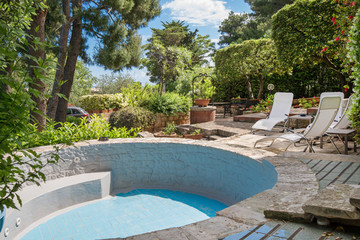 Sunbathing beds next to small pool full with clear blue water in the backyard of beautiful villa close to the sea. Concept of summer party, relaxation and luxury lifestyle.