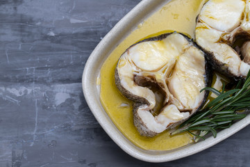 boiled fish with olive oil and rosemary in dish