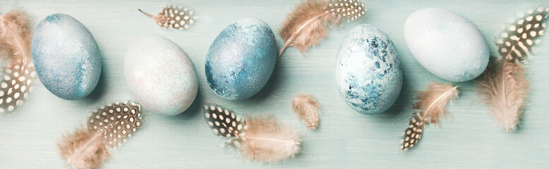 Painted traditional eggs for Easter holiday and feathers over light blue background, top view, wide...