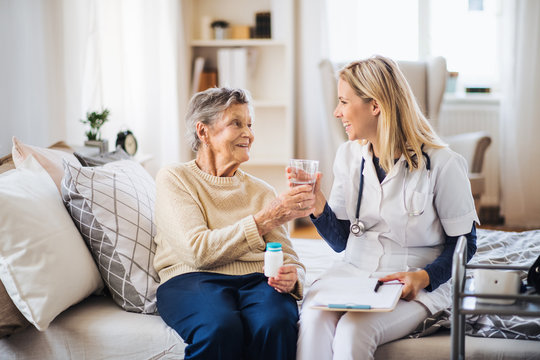 A health visitor giving a senior woman a glass of water to take pills.