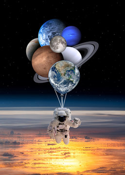 Astronaut spaceman with planets shaped balloons in solar system. Elements of this image furnished by NASA.