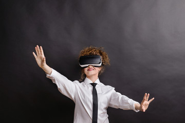 Portrait of a young woman with virtual reality goggles in a studio.