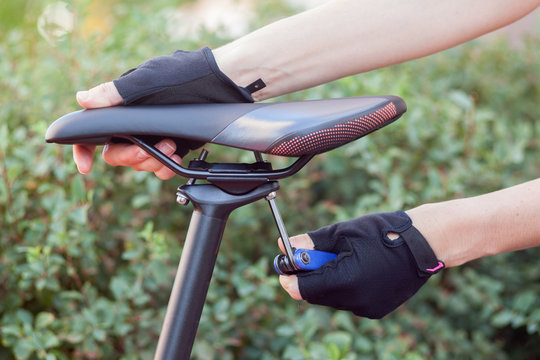 Black saddle against a street background.  The hand with the multitool twists the mount on the seat.