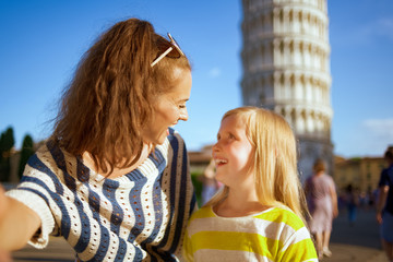 mother and daughter against leaning tower in Pisa taking selfie
