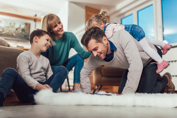Happy family having fun on floor of in living room at home, laughing.