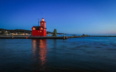 Holland Michigan Lighthouse At Night. The beautiful big red lighthouse at Holland State Park at night with illuminated beacon.
