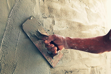 construction worker plastering cement on wall