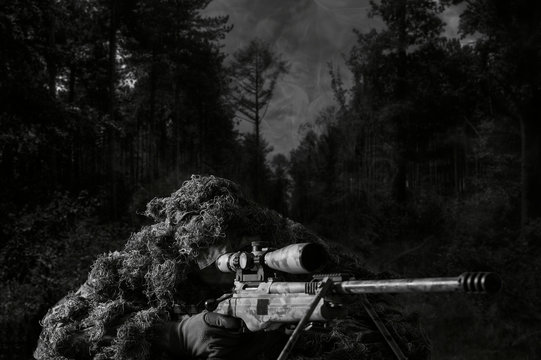 The sniper in disguise lies with a sniper rifle and aims at the telescopic sight.