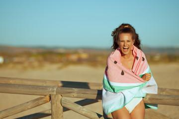 woman on ocean coast in evening wrapped in watermelon towel
