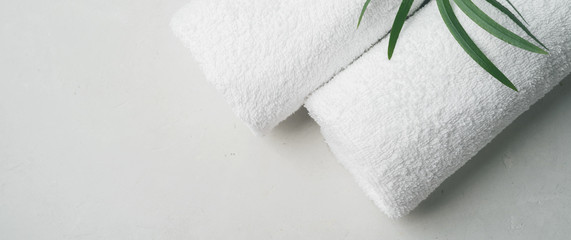 Spa concept: two white fluffy towels twisted into rolls on a light surface with a palm leaf with copy space, flat lay