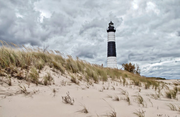 Lighthouse Beach Background. The Big Sable Lighthouse on the coast of Lake Michigan surrounded by dune grass and sand dunes at Ludington Stat Park in Michigan.