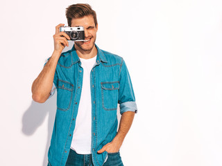 Portrait of handsome smiling man wearing summer hipster jeans clothes. Model male holding vintage photo camera. Isolated on white