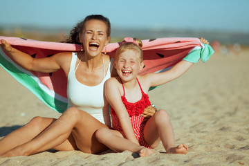 mother and child holding funny watermelon towel while sitting