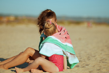 mother and daughter wrapped in watermelon towel spending time
