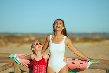 smiling mother and daughter on beach in evening having fun time