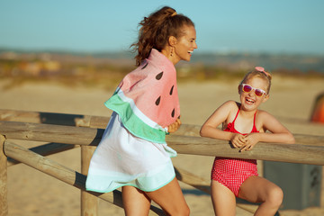 mother and daughter on ocean coast in evening having fun time