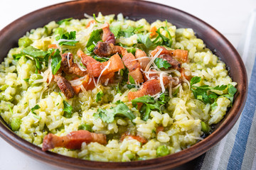 Traditional Italian risotto with peas, carrots and fried bacon, pancetta in rustic style, close-up