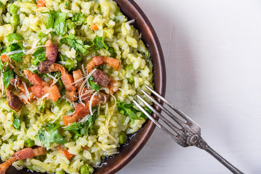 Traditional Italian risotto with peas, carrots and fried bacon, pancetta in rustic style, close-up, copy space for recipe
