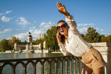 smiling traveller woman using smartphone and waving for someone