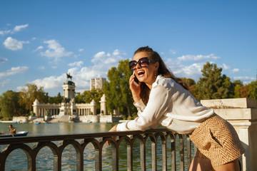 woman at El Retiro Park in Madrid, Spain using mobile phone