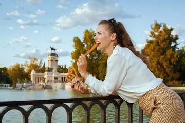 tourist woman in Madrid, Spain eating traditional Spain churro