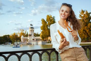 tourist woman at El Retiro Park eating traditional Spain churro