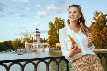 happy stylish traveller woman eating traditional Spain churro