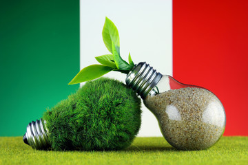 Green eco light bulb with grass, plant growing inside the light bulb, and Italy Flag. Renewable energy. Electricity prices, energy saving in the household.