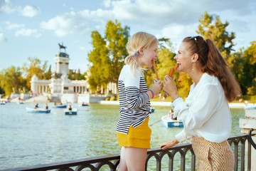 mother and daughter travellers eating traditional Spain churro