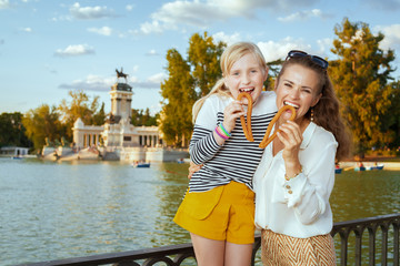 mother and daughter tourists eating traditional Spain churro