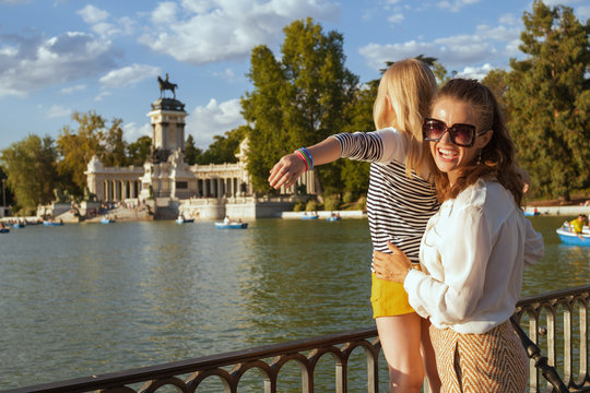 happy mother and child tourists at Park del Retiro rejoicing