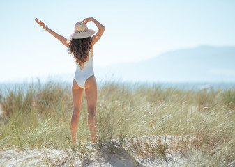 young woman in white beachwear on beach rejoicing