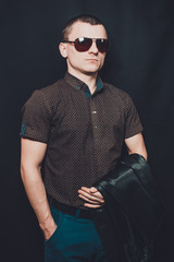 portrait of a sexy man dressed in a black shirt and brown sunglasses