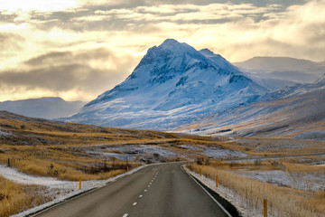 Long road curve in iceland with snow mounrtain background. afternoon time gold cloud
