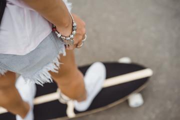 girl with long hair skates on a skateboard. street, active sports