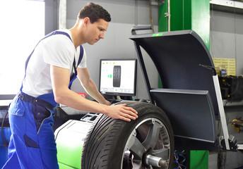 tyre change in a garage - assembler balancing a tyre on the machine // Automechaniker wuchtet neuen PKW Reifen an Maschine für Montage aus