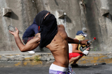 Demonstrators clash with Venezuelan National Guards during a protest close to one of their outposts in Caracas