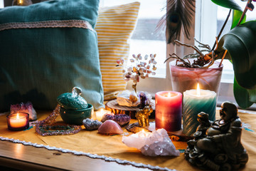 Feng Shui altar at home in living room or bed room. Attracting wealth and prosperity concept. Crystal clusters, wire tree with gemstones, golden Buddah figure on table and window sill. Vibrant colors.