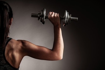 Beautiful young woman workout with dumbbell over gray background in fitness gym club