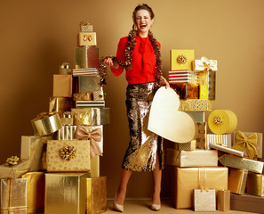 happy trendy shopper woman with golden heart and tinsel