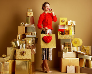 happy woman with shopping bag and red heart using mobile phone