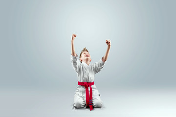 Creative background, a child in a white kimono rejoices victory, on a light background. The concept of martial arts, karate, sports since childhood, discipline, first place, victory. copy space.