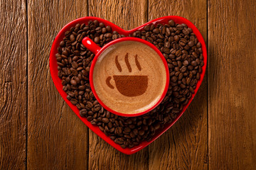 Red cup and coffee saucer in heart shape with decorated coffee on old wood background. Top View. cup shape in coffee