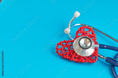stethoscope and red heart on blue background, medical care