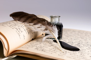 Old writing feather and ink spot with handwritten letter in background