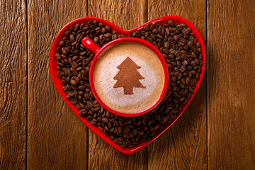 Red cup and coffee saucer in heart shape with decorated coffee on old wood background. Top View. Christmas tree shape in coffee.