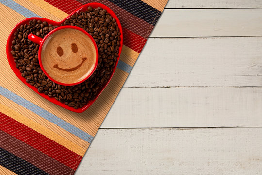 Red cup and coffee saucer in heart shape with decorated coffee on old wood background. Top View. Smile shape in coffee